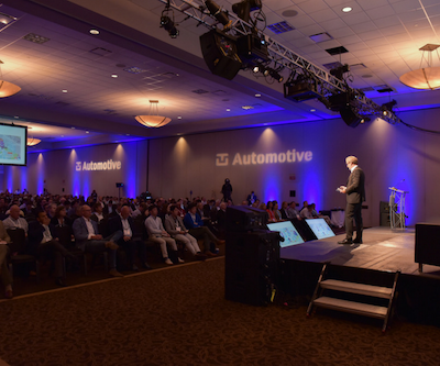 A speaker presenting on stage to a large and engaged audience at ADAS and Autonomous Vehicles USA conference